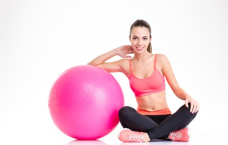 fitball: Beautiful happy fitness girl in tracksuit sitting and posing with pink fitball isolated over white background Stock Photo