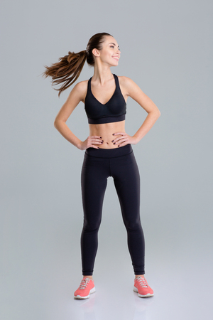 sportwear: Happy beautiful fitness girl in sportwear warming up her neck over grey background Stock Photo
