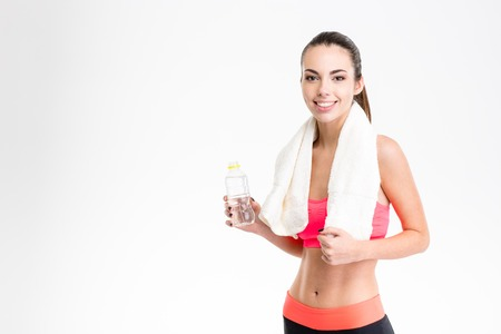 Portrait of cheerful pretty young fitness woman with white towel on her neck and bottle of water over white background