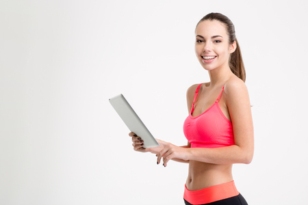 sportwear: Positive attractive young fitness woman in sportwear holding tablet over white background