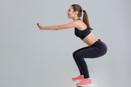 Attractive young sportswoman in sportwear doing squats isolated over grey background