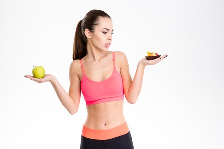 tempted: Portrait of tempted attractive fitness woman making food choice isolated over white background