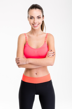 slim women: Beautiful smiling young sportswoman in pink top and black   leggings standing with crossed arms isolated over white background