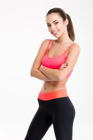 Portrait of a smiling fitness woman standing with arms folded and looking at camera isolated on a white background