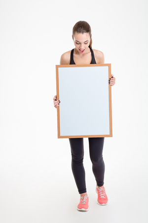 a placard: Pretty excited fitness girl in sportwear holding blank board in front of herself and looking on it over white background Stock Photo