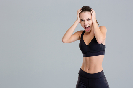 Crazy hysterical shouting fitness girl in black top and leggings isolated over grey background Stock Photo