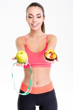cintas: fitness mujer hermosa linda alegre en polainas negras superior e rosa de toma de decisiones entre la manzana y pastel sobre el fondo blanco
