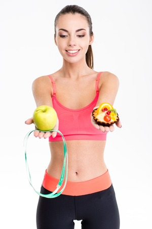 woman eating fruit: Joyful cute lovely fitness woman  in pink top and black   leggings making decision between apple and cake over white background