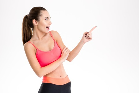 sportwear: Excited content pretty fitness girl in sportwear pointing away and looking away over white background