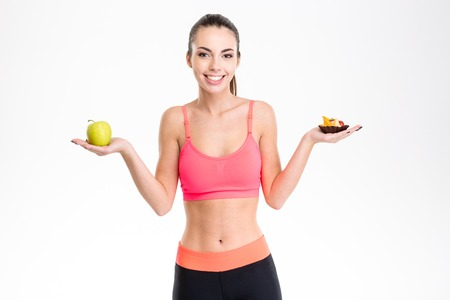 right choice: Cheerful young fitness girl holding healthy and unhealthy food, trying to make the right choice over white background Stock Photo