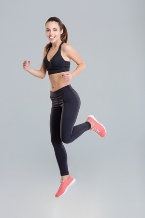 active wear: Cheerful active young sportswoman in fitness wear running isolated over grey background
