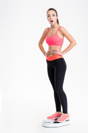 wondered: Full length portrait of beautiful wondered young fitness woman in pink top and black leggings standing on weighing scale over white background