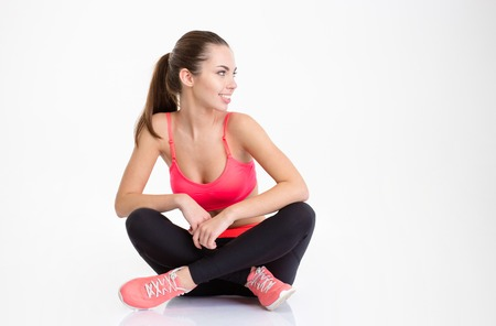 legs folded: Happy smiling young fitness woman sitting with folded legs and looking away isolated over white background