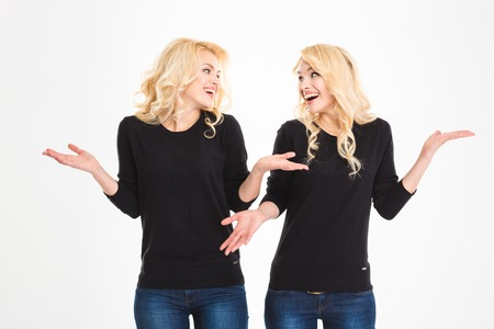 Portrait of a laughing sisters twins looking at each other and shrugging shoulders isolated on a white background Stock Photo
