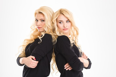 egoist: Portrait of a young serious sisters twins standing back to back with arms folded isolated on a white background