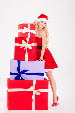 Full length portrait of a happy woman in santa cloth standing with gift boxes isolated on a white background
