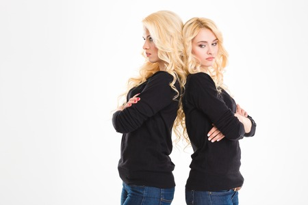 offended: Portrait of a young offended sisters twins standing back to back isolated on a white background