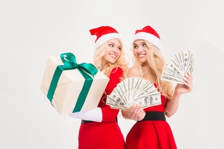 Beautiful happy sisters twins in red santa claus clothes and hats  with money and gift isolated over white background Stock Photo