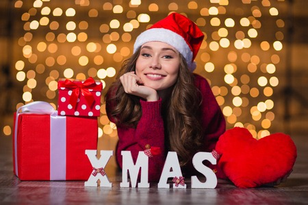 and spelling: Cheerful beautiful girl in santa claus hat lying near letters spelling word Xmas over holidays lights background