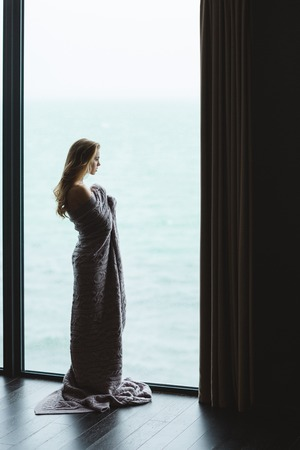coverlet: Full length portrait of beautiful thoughtful young female with long hair standing in knitted coverlet