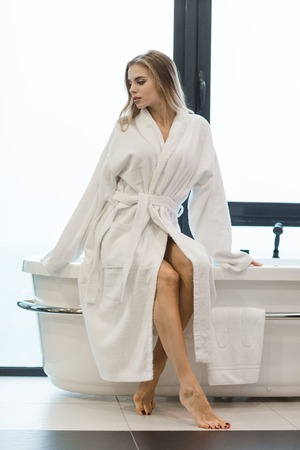 Beautiful sensual barefooted female in white bathrobe sitting on bathtub in bathroom