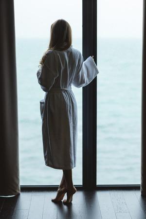 パノラマ ビューの窓近くのつま先で美しいスリムな女性立っているの背面図