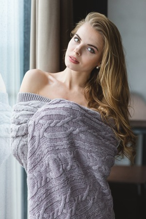 coverlet: Beautiful tempting young woman with long hair standing near window in knitted coverlet Stock Photo