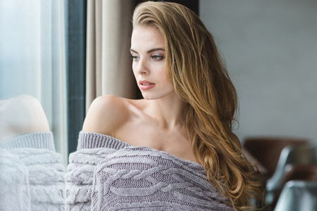 coverlet: Portrait of seductive blonde young female with long hair wrapped in grey knitted coverlet