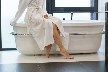 Attractive young barefooted woman in white bathrobe sitting on bathtub in bathroom
