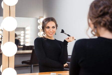 woman mirror: Portrait of a happy woman looking in the mirror and applying cosmetic with brush Stock Photo