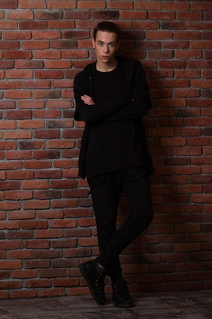 men standing: Full length portrait of a casual man with arms folded standing over brick wall background
