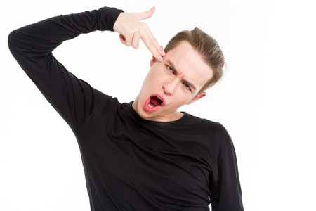 facial gestures: Portrait of a young man showing gun gesutre over his head isolated on a white background