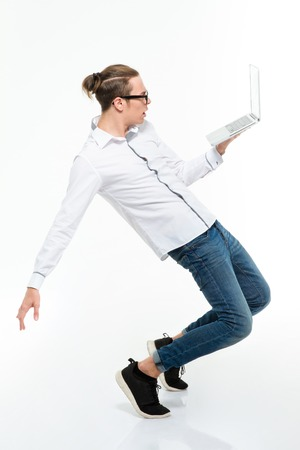 computer dancing: Full length portrait of a young casual man dancing with laptop computer isolated on a white background
