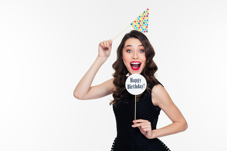 白い背景に分離された誕生日小道具でポーズのレトロなスタイルで明るいメイクでかなり巻き毛若い女性をうれしそうな笑顔 写真素材