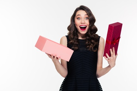 Happy amazed retro styled woman with curly hair in black dress opened present over white background Фото со стока