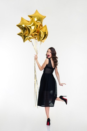 Attractive playful happy woman with retro hairstyle in classic black dress and shoes looking back and holding golden balloons
