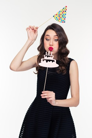 Cute lovely  curly retro styled young woman in black dress blowing on fake birthday cake with candles props and holding birthday hat booth over white background Stock Photo