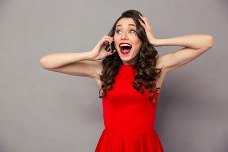 Portret van een gelukkige verbaasde vrouw in een rode jurk praten over de telefoon over grijze achtergrond Stockfoto