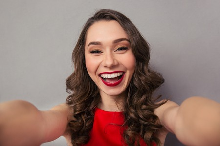 woman only: Portrait of a cheerful woman making selfie photo over gray background