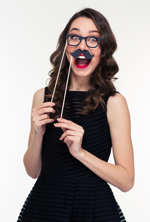 Funny cheerful young woman with bright makeup in retro style having fun using glasses and moustache props over white background Stock Photo