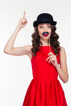 women: Playful hilarious young curly woman in red dress and funny black hat with light bulb having fun with moustache props and pointing up Stock Photo