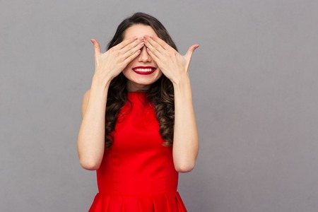 expresiones faciales: Portrait of a smiling woman in red dress covering her eyes over gray background
