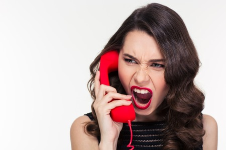 Close up of angry mad curly young woman in retro style screaming and talking on telephone over white background