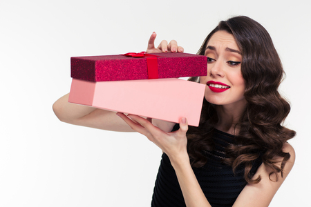 anticipated: Anticipated attractive curly young woman in retro style opening present box over white background