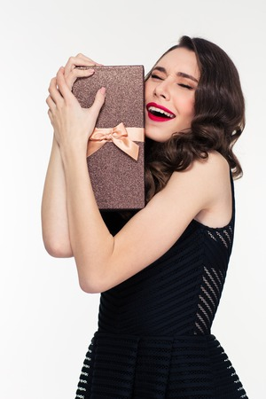elated: Excited elated pretty young woman with retro hairstyle in black dress hugging gift box over white background