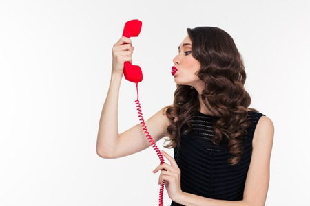 Cute lovely curly young woman in retro style sending kiss into telephone receiver over white background