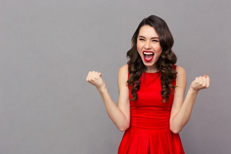 Portrait of a cheerful woman in red dress celebrating her success over gray background