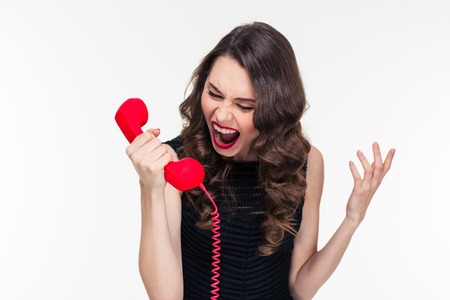raged: Crazy raged retro styled curly young female shouting in red telephone receiver over white background