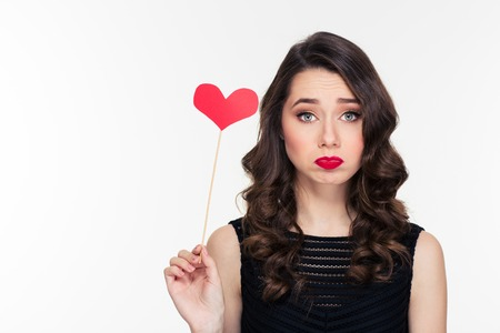 lonely heart: Cute lovely sad curly girl with bright makeup in retro style holding heart booth isolated over white background