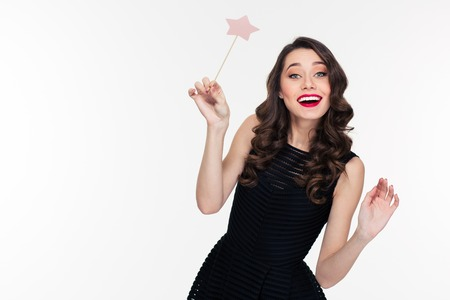 wand: Cheerful beautiful curly young woman with retro hairstyle in black dress posing with magic wand over white background Stock Photo